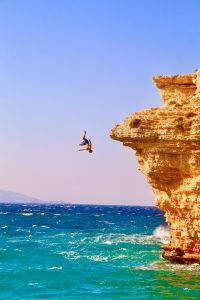 A person cliff diving into the ocean